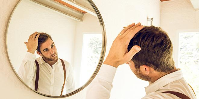 Man grooming his hair in front of a mirror.